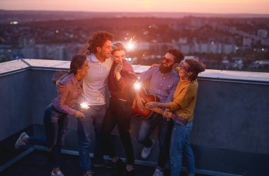 Young friends with sparklers enjoying party on rooftop