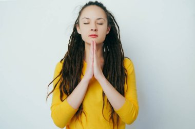 Beautiful girl with dreadlocks and in a yellow bright sweater prays by slapping his hands in a religious impulse. Asks for the help of God.