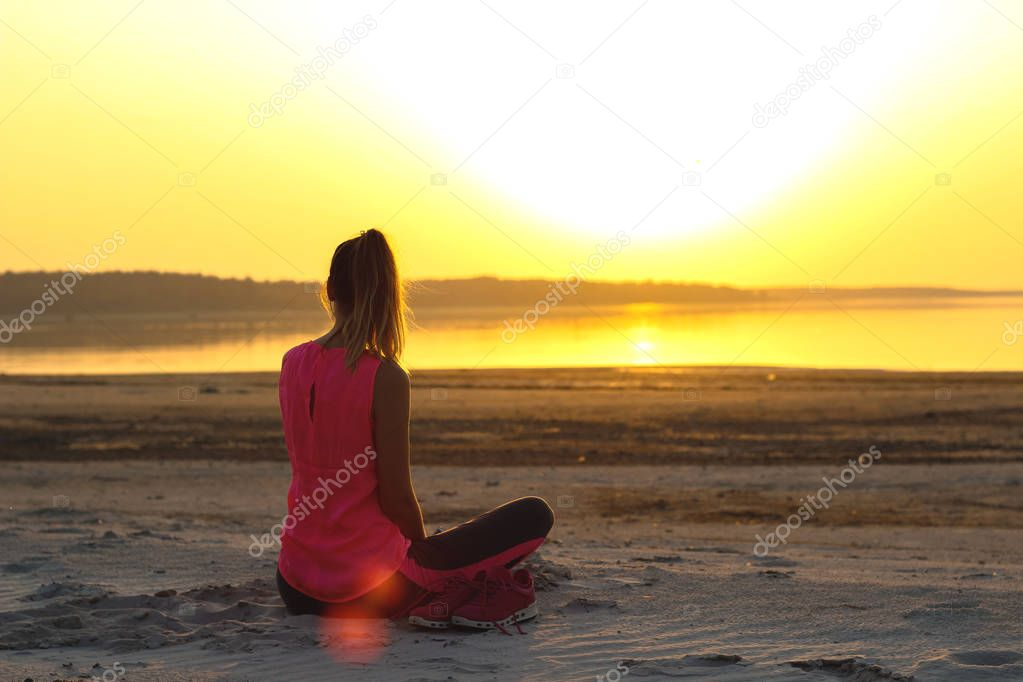 Young beautiful girl in sportswear sits on a sandy beach and enjoys an orange sunset by the sea and listens to music in her mobile phone.