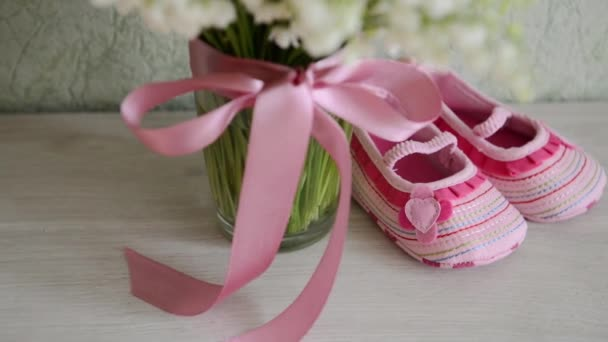 childrens shoes are on the table near a bouquet of flowers. For a baby shower celebrate. for thematic birthday decor