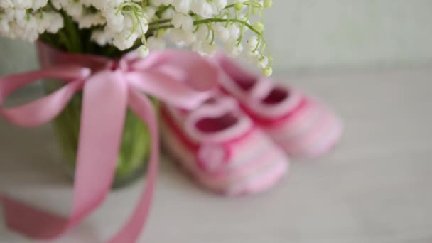 Childrens Shoes Are On The Table Near A Bouquet Of Flowers For A