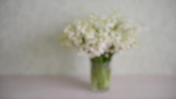 on the table in the room is a white bouquet of fresh wild valley lilies in a transparent mug