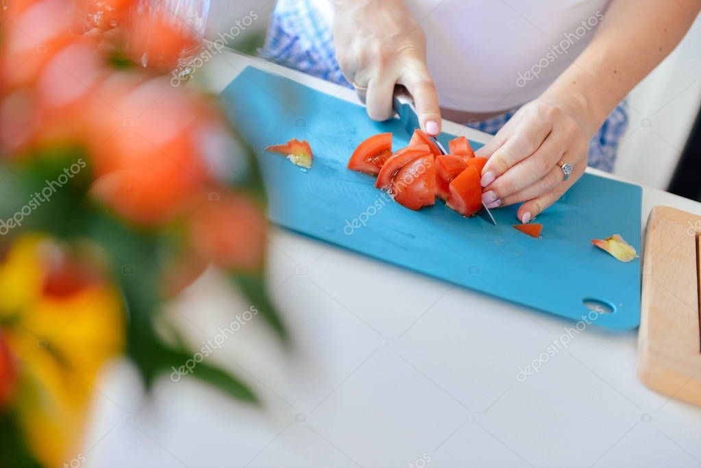 on the table, cooking products, sausages and tomatoes, cut with a knife