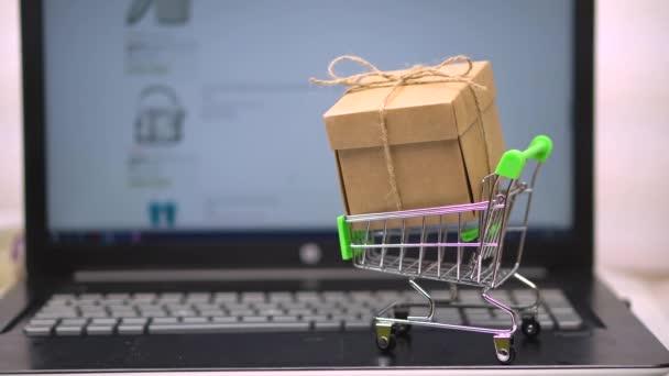 Box piaci kocsi egy laptop billentyűzet. a háttérben egy online élelmiszerbolt. online bevásárlás a Házhozszállítással