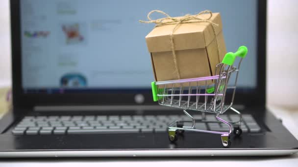 Box in market trolley on a laptop keyboard. against the background of an online grocery store. online shopping for home