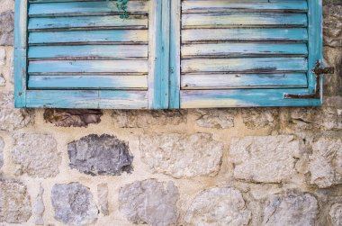 Old stone wall with closed shutters window
