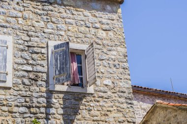 Stone wall with wooden shutters on the window