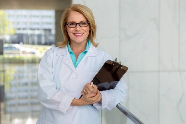 Female nurse, doctor, health care practitioner, standing lifestyle working portrait in hospital hallway, smiling and cheerful