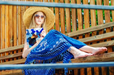 Young girl in sunglasses in a straw hat reads a glossy magazine on a bench on a background of a wooden wall. Summer mood, relaxation