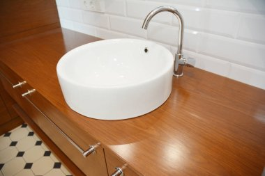 Bathroom ceramic sink with chome water tap and wooden table.