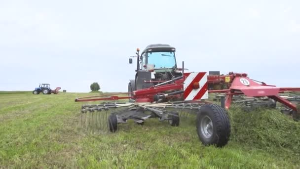 Traktor fährt auf Feld mit Mähdrescher Gras