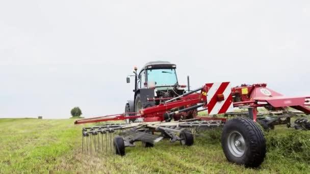 Traktor mezőgazdasági területen a lovaglás összeköt kocsi fű gyűjtése