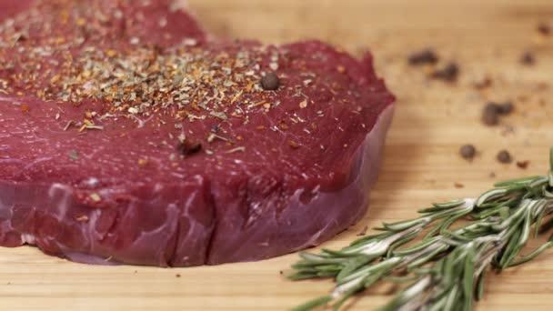 Koření kapky na kus syrové čerstvé červené hovězí steak na stole