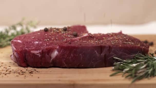 Kus syrového červeného masa na stole s rozmarýnem a koření