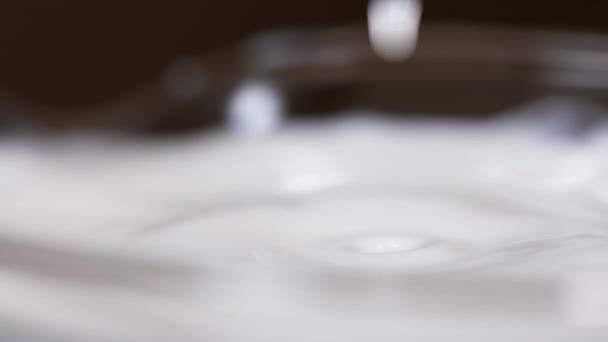 Goccia di latte puro cade in vetro rendendo ripple sulla superficie