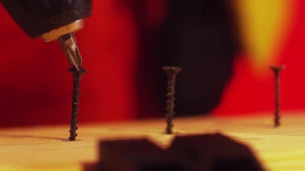 Carpenter řídí 3 šrouby do nezpracovaného dřevěné prkno s elektrický šroubovák