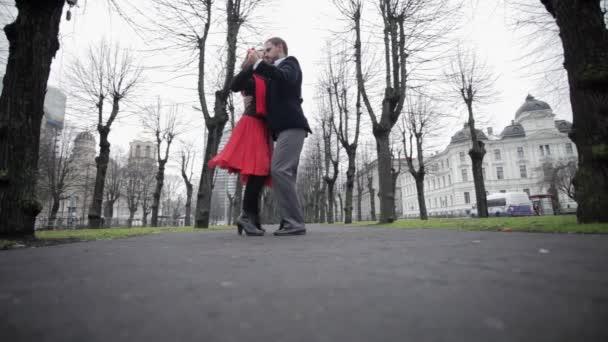 Mladý roztomilý kluk a holka se citově tančí v ulici mezi nahé stromy