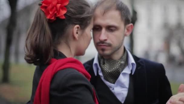 Vousatý muž a žena s červeným šátkem se tančí v prázdné ulici letní