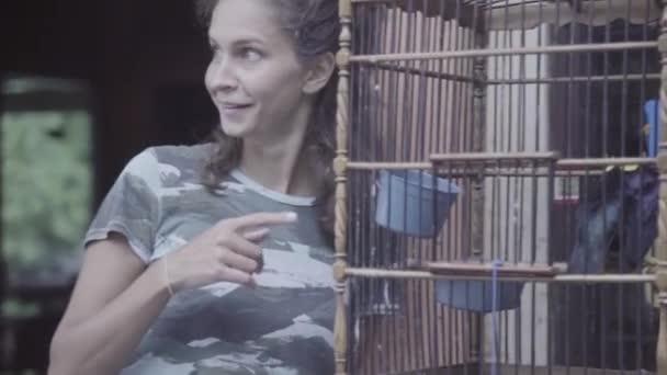 Zralá žena s ohromen tváří body s prstem na velké dřevěné klece s ptákem