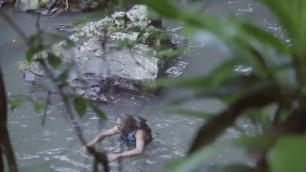 Zwei junge Männer mit Schwimmen Westen sind im sprudelnden Fluss im Wald schwimmen.