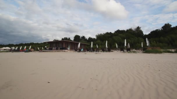 Empty yellow sand beach of small brown modern wooden resort on cloudy windy day.