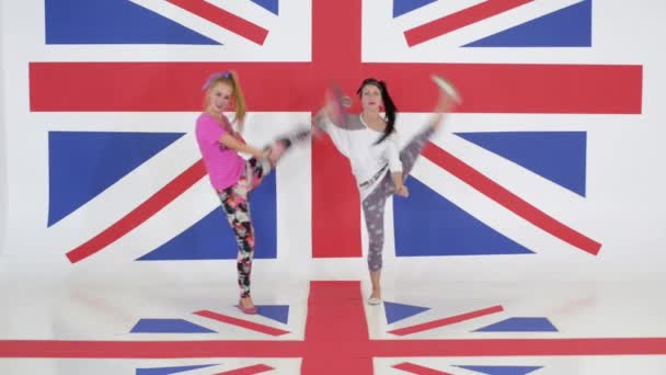 Rehearsal of two charismatic females dancing on background of british flag