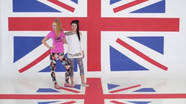 Prove di due interpreti di danza ragazze divertenti su sfondo di texture di bandiera del Regno Unito.