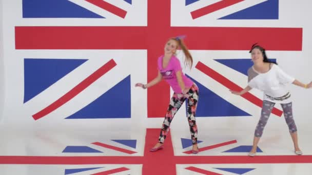 Two pretty smiling girls are dynamically dancing on background of british flag