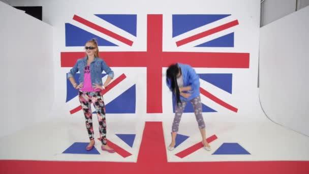Dvě mladé ženy praktikují dynamický tanec na pozadí britské vlajky