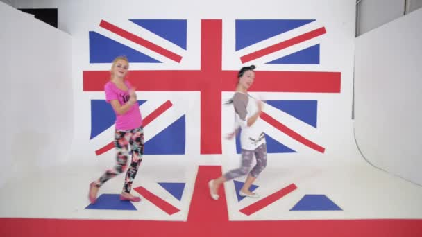 Two caucasian enetgetic girls do dancing workout on background of british flag