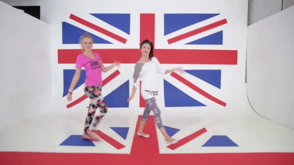 Two charming caucasian smiling girls with long black and red hair , dressed in bright clothes are synchronically and energetically dancing on camera on background of british flag.