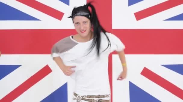 Mladá bruneta žena je dynamicky tančí na pozadí britské vlajky
