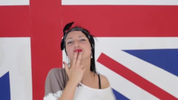 Atraktivní tmavovlasá dívka tance emotinally na pozadí vlajky Velké Británie