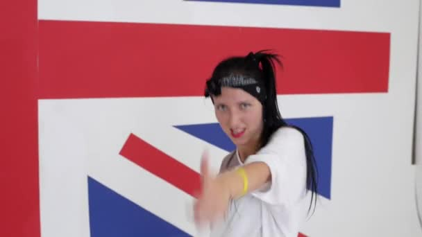 Hezká černovlasá dívka tance energicky na pozadí vlajky Velké Británie