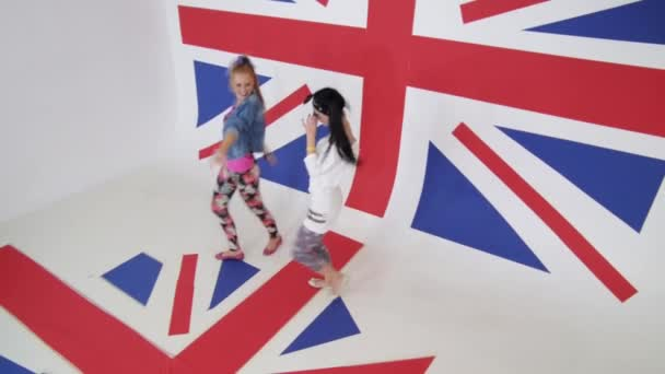 Two nice-looking girls are energetically dance standing on british flag.