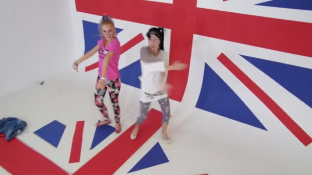 Mladé ženy v barevných šatech se radostně tančí na britské vlajky