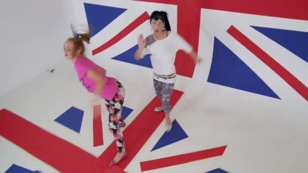 Krásné ženy v barevných šatech se radostně tančí na pozadí Uk vlajka