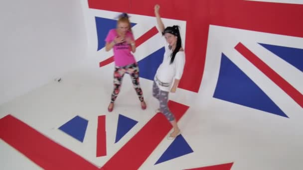Atraktivní ženy v moderním oblečení se radostně tančí na britské vlajky