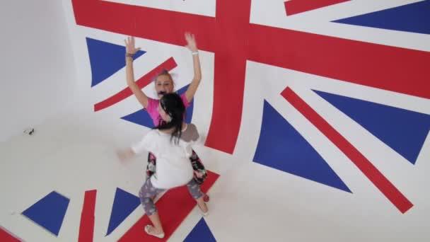 Krásné ženy v barevných šatech se sexuálně tančí na britské vlajky