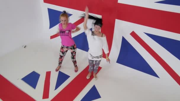 Pretty girls in colored clothes are sexually dancing in studio with british flag