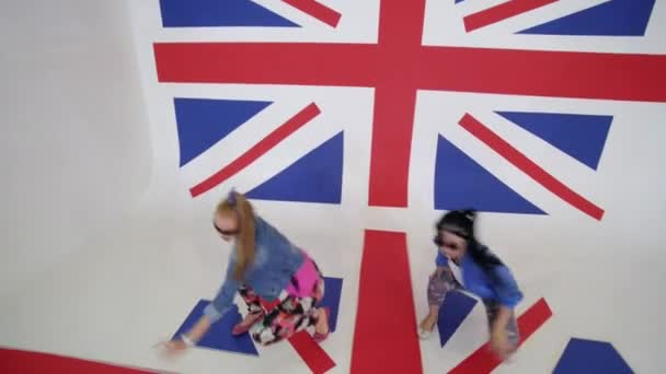 Hot young women in sunglasses workout dance moving in studio with UK flag