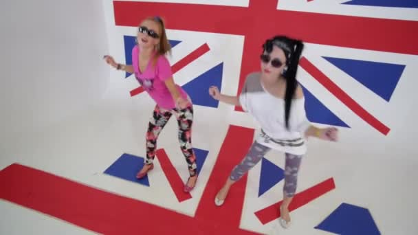 Sexy young women in sunglasses workout synchronic dancing in studio with UK flag