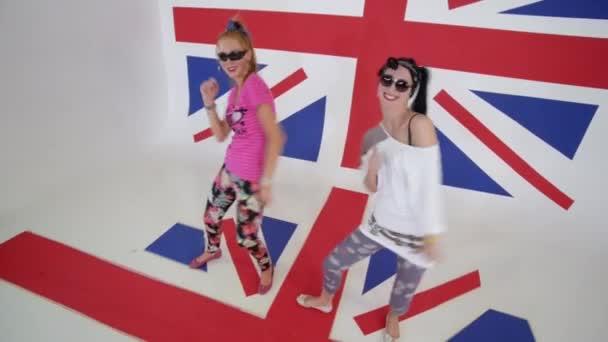 Hezké mladé ženy v sluneční brýle jsou zíral na kameru a flexikuritě tanec