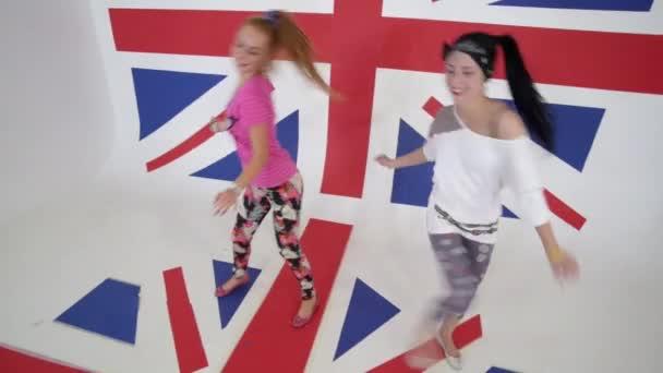Usmívající se dívky v tričkách podívat na kameru a tančit v bílých studio s vlajkou Velké Británie