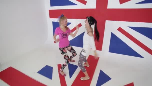 Usmívající se ženy v tričkách podívat na kameru a tančit v bílých studio s vlajkou Velké Británie