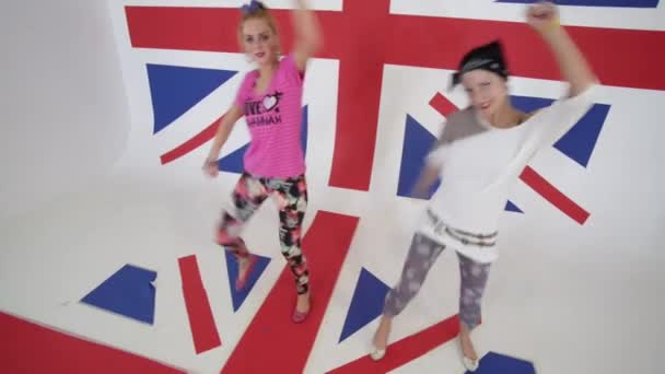 Cute funny smiling girls look at camera and dance in white studio with UK flag