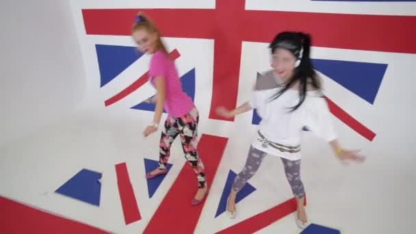 Roztomilý funny úsměvem ženy podívat na kameru a tančit v bílých studio s vlajkou Velké Británie