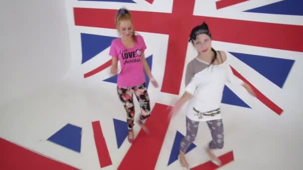 Roztomilá aktivní dívky podívat na kameru a tančit v bílých studio s velkým Uk vlajka