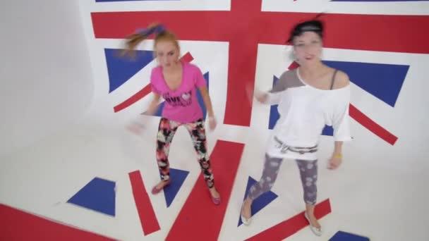 Dvě tanečnice podívat na kameru a pohybovat v bílém studio s velkým Uk vlajka