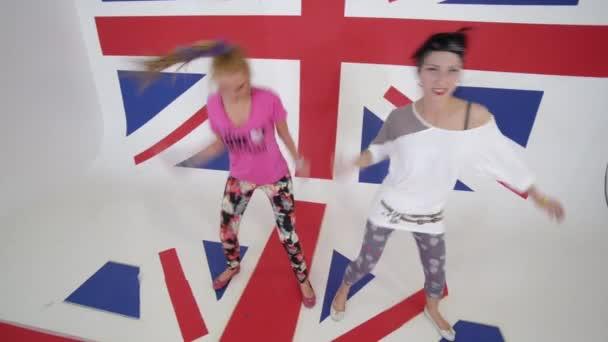 Hezká žena tanečnice podívat na kameru a pohybovat v bílém studio s velkým Uk vlajka